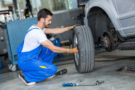 mechanics: Auto mechanic removing wheel of a car in a workshop