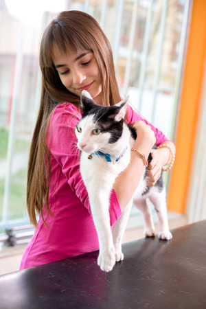 restless: Girl with her restless sick cat trying to calm her down at vet clinic Stock Photo