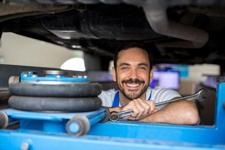 Satisfied male mechanic under car