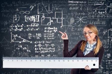 nombres: �tudiante souriante femme avec un grand chef pointant formules sur fond Banque d'images