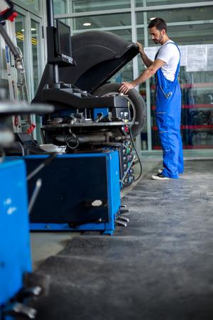 technician: mechanic balancing  car wheel on balancer