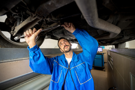 underneath: A mechanic is checking the technical state underneath a car Stock Photo