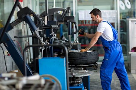 pneumatic tyres: repairman balancing  car wheel on balancer in workshop Stock Photo
