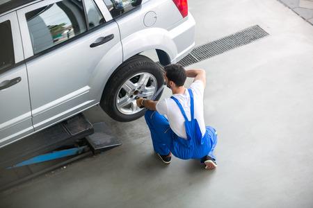 mechanic: Mecánico que quita un neumático de un coche con una llave de aire
