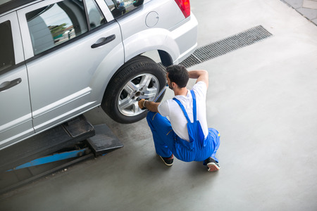 automobile tire: Mechanic removing a tire from a car with an air wrench