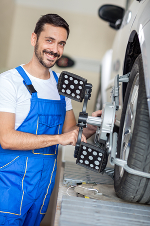 aligning: serviceman checking wheel alignment in a car workshop