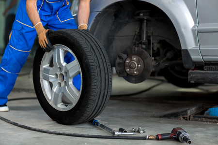 워크숍에서 현대 자동차의 바퀴를 변경하는 정비공 스톡 콘텐츠