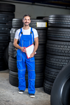 tire repair shop: mechanic checing clipboard car tires in tire store Stock Photo