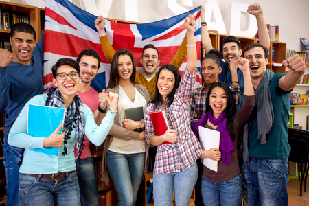 girl studying: Cheerful British students with raised fists and flag of United Kingdom celebrate victory