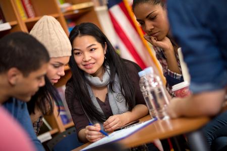 Groupe multiethnique d'étudiants travaillant ensemble sur la tâche Banque d'images