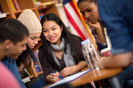 tasks: Multiethnic group of students working on task together Stock Photo