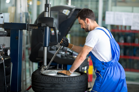 pneumatic tyres: mechanic replace tires on wheels in a workshop Stock Photo
