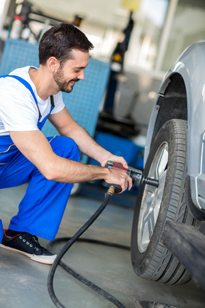 impact wrench: Auto mechanic changing tyre on car with pneumatic wrench Stock Photo