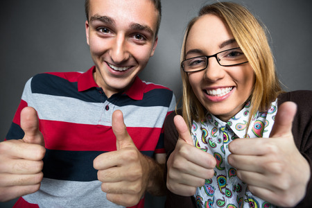 nerdy: Laughing nerdy couple showing thumbs up