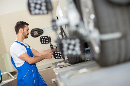 mécanicien automobile installation du capteur pendant le réglage de la suspension