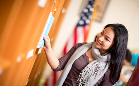 choose university: Beautiful young Asian student choosing book in library Stock Photo