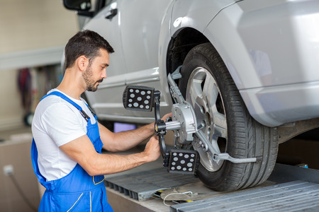 car mechanic installing sensor  adjustment and automobile wheel