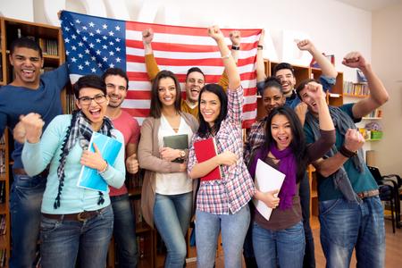 idiomas: Sonriendo estudiantes estadounidenses que presentan su país con banderas