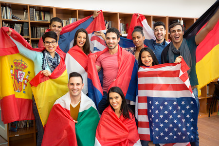 International multiethnic exchange of students, happy students presenting their countries with flags Stockfoto