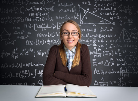 Smiling female student siting front open book and learning Stock Photo