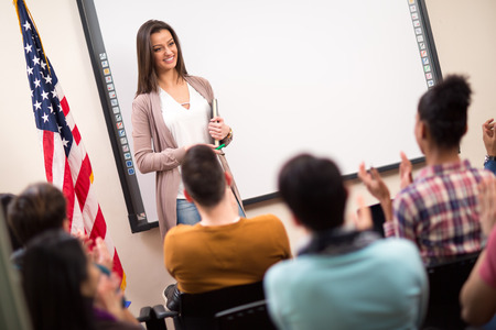 clapping hands: Good looking assistant finished lecture and students clapping hands Stock Photo