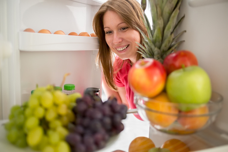 refrigerator with food: Smiling woman look at grape and apple in refrigerator