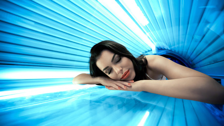 Jeune femme ayant bronzage traitement de la peau dans le solarium Banque d'images