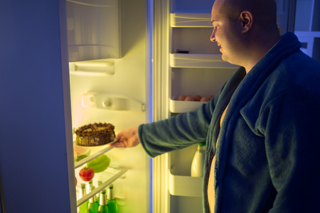 refrigerator: Fat man at night overstep and take whole chocolate cake from refrigerator