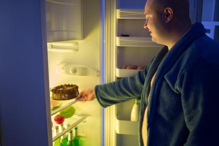 malos habitos: Hombre gordo en la noche overstep y tomar tarta de chocolate entera del refrigerador Foto de archivo