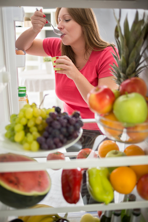 eating right: Pretty female sweetens with fresh fruit yogurt from refrigerator