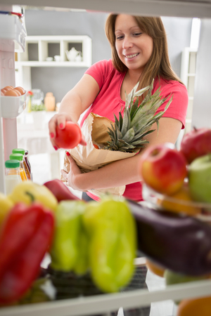 purchase: Young woman from purchase  full fridge with fruit and vegetables Stock Photo