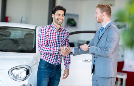 automobile dealership: salesman and client at the car saloon, sitting, gesturing and presenting selling conditions
