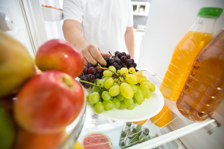 refrigerator with food: Grapes and apples in refrigerator ideal for diet