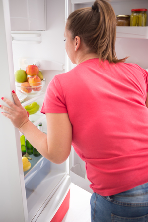 eating right: Young gourmand woman think what to take to eat from fridge Stock Photo