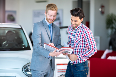 car dealership: Male Caucasian salesman and male client at the car dealership saloon indoors