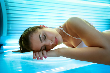 brown skin: young woman laying on solarium bed and get brown skin tone ready for summer