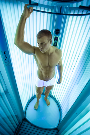 tanning: Young man in modern solarium, tanning skin treatment Stock Photo