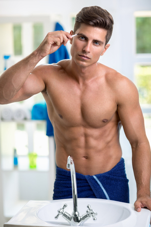 muscled: Man removing eyebrow hairs with tweezing front of mirror