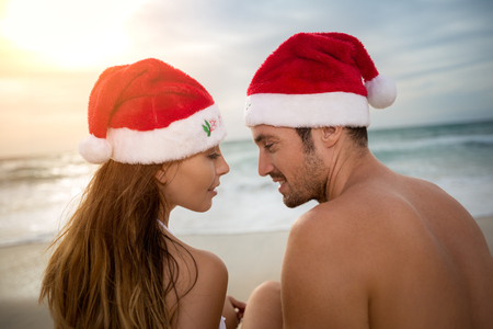 romantic beach: Couple in love with Santa hats on beach almost kisses Stock Photo