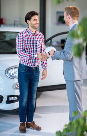 buy car: Seller or car salesman and customer in dealership, they shaking hands and seal the purchase of the auto or new car.