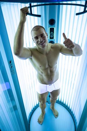 solarium: Happy man in solarium showing thumbs up