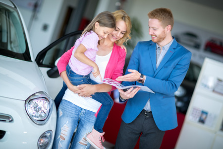 brand new: Young smiling mom holding her daughter in car showroom Stock Photo