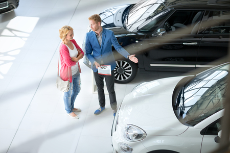 car salesperson: Friendly car dealer showing young women new car in showroom