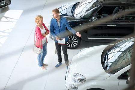 rental: Friendly car dealer showing young women new car in showroom