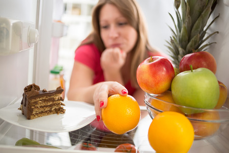Woman hesitating whether to eat piece of chocolate cake or orange Stock Photo