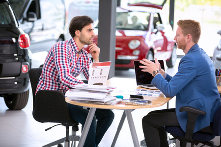 car agent talking with male customer at car dealership saloon Stock Photo