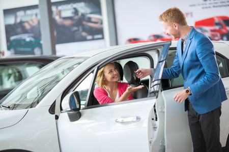 sales manager: Sales manager giving key from the new car female client
