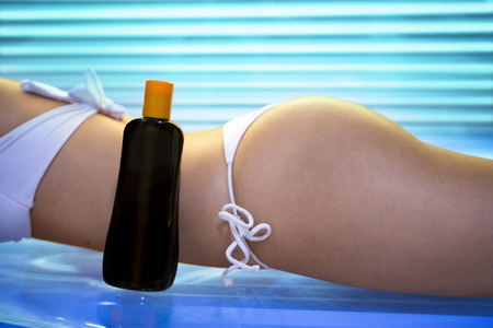 light complexion: Sexy female body on tanning bed with bronzing oil - Beauty, healthcare.