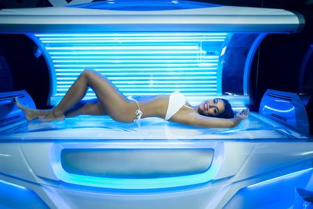 Belle jeune femme ont bronzage traitement de la peau dans le solarium moderne Banque d'images