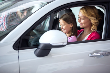 Young woman with daughter sitting in car at car dealership saloon
